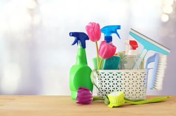 Spring cleaning concept with supplies on wooden table.
