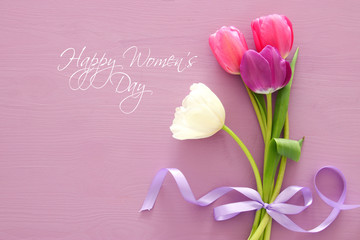 bouquet of pink and white tulips over pastel wooden background. Top view. International women day concept.