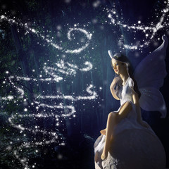 image of magical little fairy in the forest sitting over the stone.