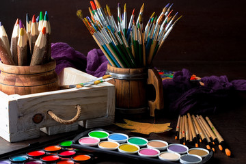 Paints for drawing and brush on a background in a composition