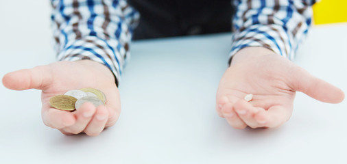 Boy's hands close-up: in one lies the tooth, in the second coins. First tooth lost.