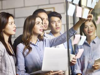 team asian and caucasian entrepreneurs meeting in office