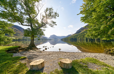 Views across Lake Buttermere from the pebble beach shore in the English Lake District on a summers day, UK.