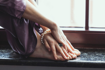 Bare feet of woman stand on granite window sill