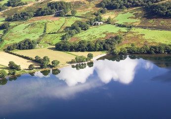 Reflections of white clouds in a blue sky on Lake Buttermere in the English Lake District, UK.