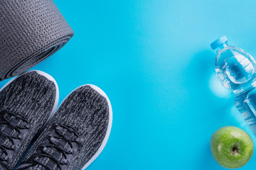 The concept of healthy lifestyle. Sport shoes, bottle of water, apple and yoga mat with copy space on blue background. Exercise equipment. Sport life, top view, flat lay.