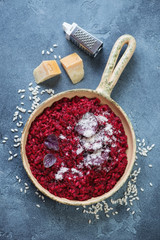 Frying pan with beetroot risotto and parmesan over blue stone background, above view, vertical shot