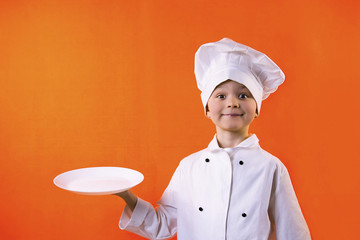 funny boy chef keeps a plate on an orange background