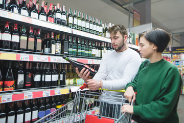 A young couple looking at a bottle of wine at a supermarket. Young couple in the alcohol department of the store
