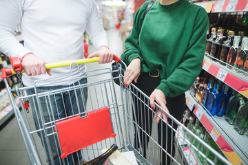 Young couple with basket for shopping in supermarket. Focus on the hands and shopping carts.