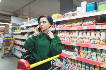 Beautiful young girl talking on the phone at the supermarket shelves. A girl with a shopping cart buys products in a supermarket