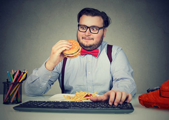 Hungry chunky man eating burger at workplace