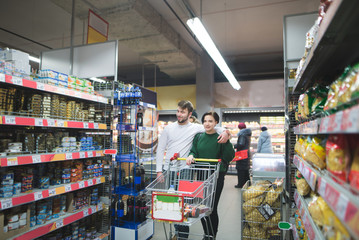 A young couple rides a supermarket with a shopping carts and buys products. Family shopping at a supermarket