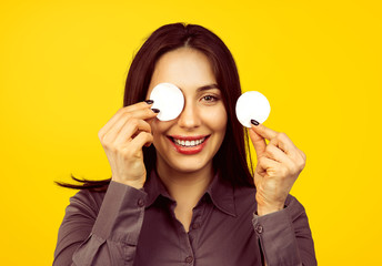 Cute woman removing applied makeup with a cotton sponge pad.