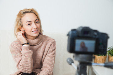 Blogging concept. Young female vlogger next to video camera at home. Beautiful woman recording vlog message at home for her internet channel