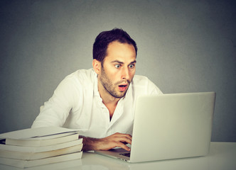 Shocked man watching laptop while studying