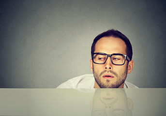 Tired office worker leaning on table
