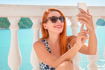 Content woman taking selfie on resort