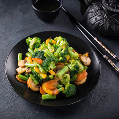 Hot stir fried vegetables on black plate. Healthy asian food concept.