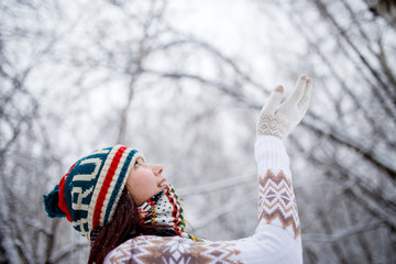 Photo of smiling girl in knitted hat and scarf catching snowflakes in winter forest during day