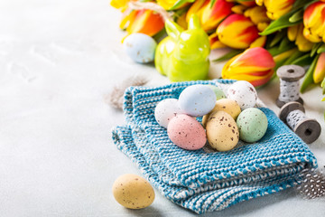 Easter greeting card with colored quail eggs candies on blue knitted napkin and tulips flowers. Spring holidays concept with copy space.