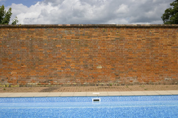 Old red brick wall contrasting with blue sky and swimming pool