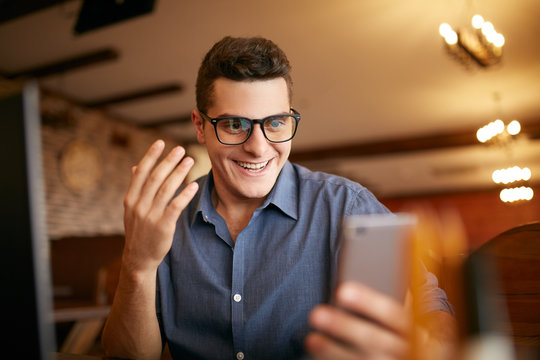 Surprised freelancer hipster man looks to smartphone and can not believe he won lottery prize or money in trading cryptocurrency. Pop-eyed successfull amazed businessman trader. Video call conference