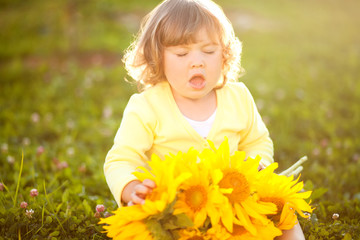 Happy child with bouquet of beautiful sunflowers.