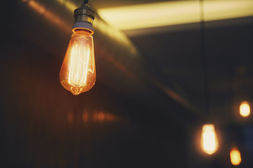 A bright warm orange lamp of Edison on a dark background. Soft processing and toning of photos. A vintage bulb hangs on the cord.