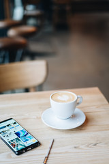 Coffee on the wooden table by the window light with Samsung galaxy note 8 on the table