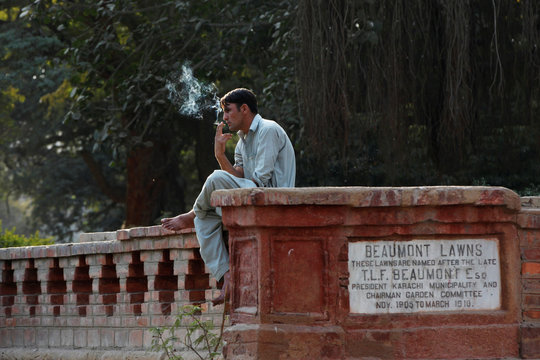 A man smokes a cigarette as he sits on a side wall of the Beaumont Lawns, in Karachi