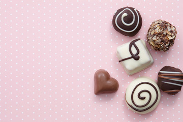Handmade chocolate candy sweets on pink background with white dots, top view