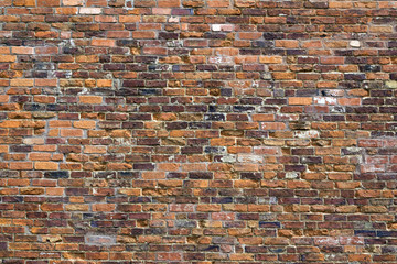 Weathered old red brick wall on a building in Winchcombe, Gloucestershire, UK.