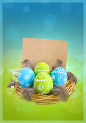 Painted Easter eggs with feathers in the nest and postcard for congratulations on green-blue blurred background