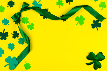 Saint Patrick's Day. Green design curved tape, green three petal clovers on yellow background