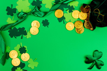 Saint Patrick's Day. Green design curved tape, green three petal clovers and little bag with gold leprechaun  coins on green background