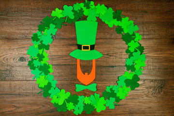 Saint Patrick's Day. Silhouette of leprechaun in hat lying on wooden background in circle shape of green three petal clovers