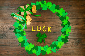 "Saint Patrick's Day. Wooden gold letters ""luck"" lying on wooden background in circle shape of green three petal clovers with gift box and gold coins"