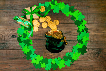 Saint Patrick's Day. Small bag of leprechaun with gold coins lying on wooden background in circle shape of green three petal clovers, gift's box and gold coins