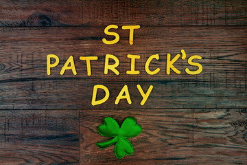 "Saint Patrick's Day. Wooden letters ""St Patrick's Day"" lying on wooden background with green three petal clover"