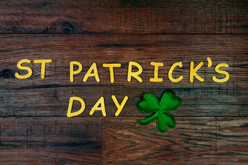 """Saint Patrick's Day. Wooden letters """"St Patrick's Day"""" lying on wooden background with green three petal clover"""
