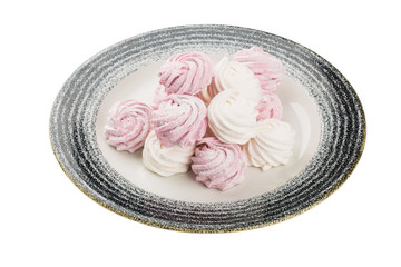 White and pink meringue in a plate. Isolated on a white background