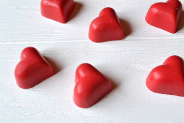Red candies on the white wooden table. Background for greeting card on Valentine's day.