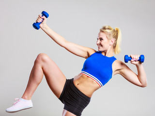 Fit woman lifting dumbbells weights