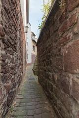 Enge Gasse mit Steinmauer in einer deutschen Altstadt