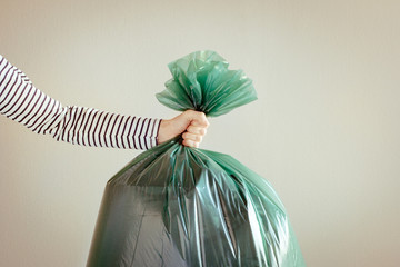 Hand, holding garbage bag.