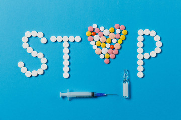 Medication white, colorful round tablets in word Stop isolated on blue background. Pills heart, ampoule, empty syringe needle. Concept of treatment choice, healthy lifestyle. Copy space advertisement.