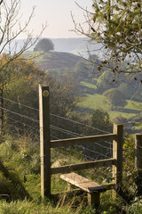 England, Cotswolds, Gloucestershire, Uley Bury, autumn  view over footpath stile to valley beyond