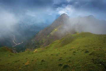 Descending grassy slope, mountain tops under thunderclouds