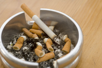 Ashtray full of extinguished cigarette butts with one lit